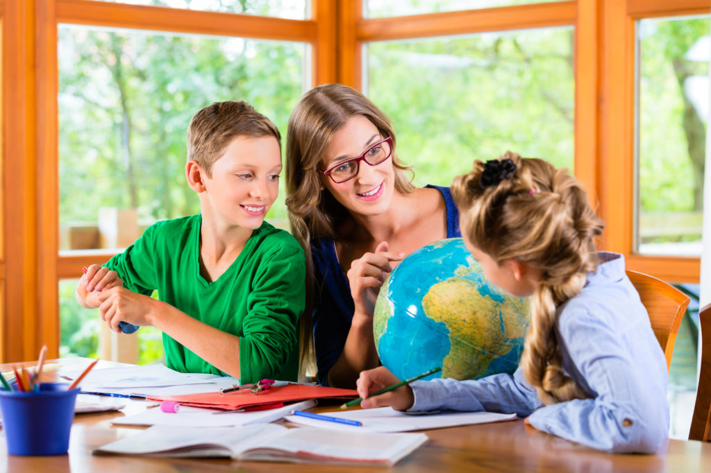 Mom pointing at a globe, homeschooling her son and daughter. Each kids has colored pencils and papers and folders on a table.