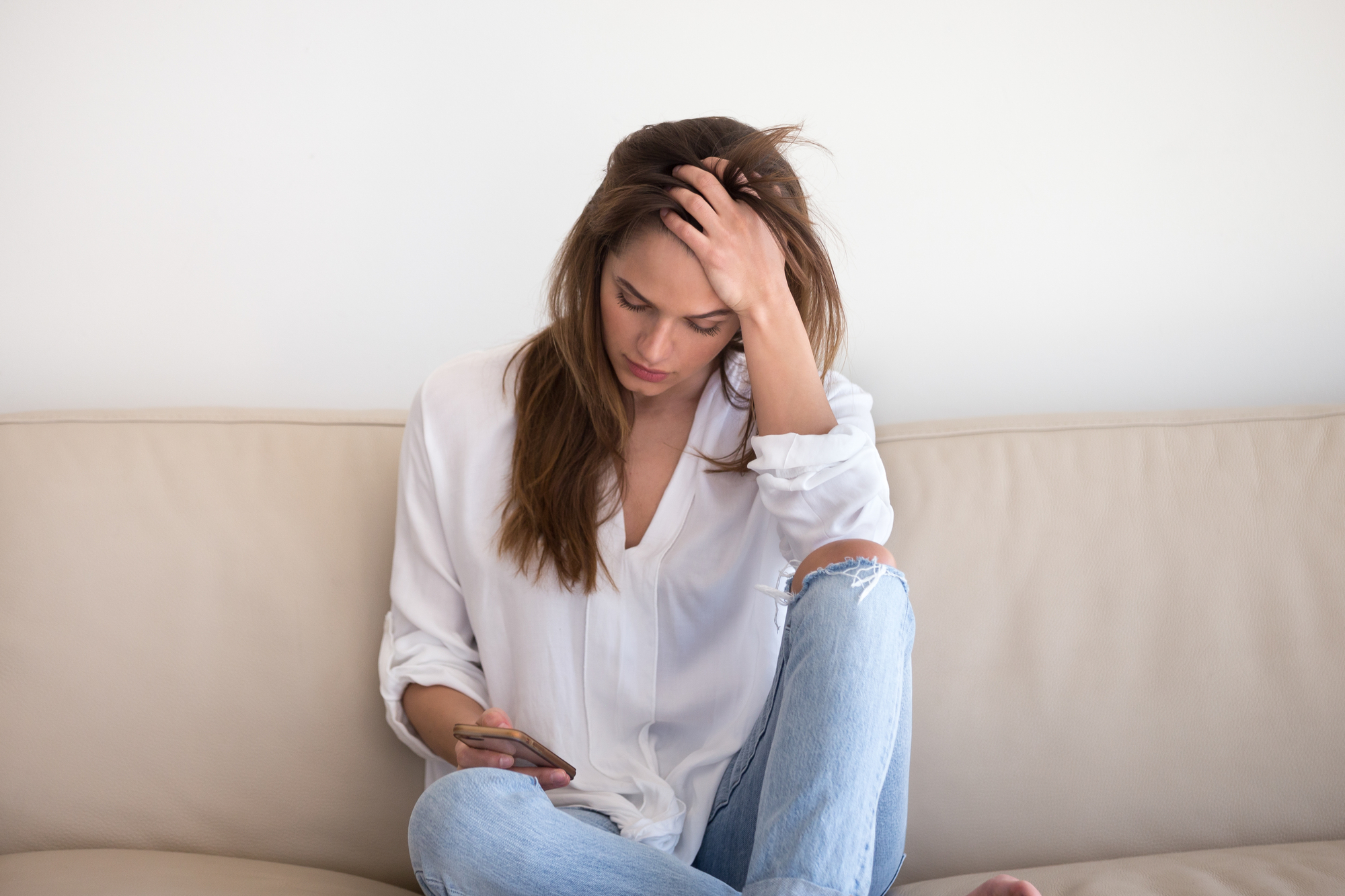 Woman sits on her sofa and  looks sadly down at her cell phone