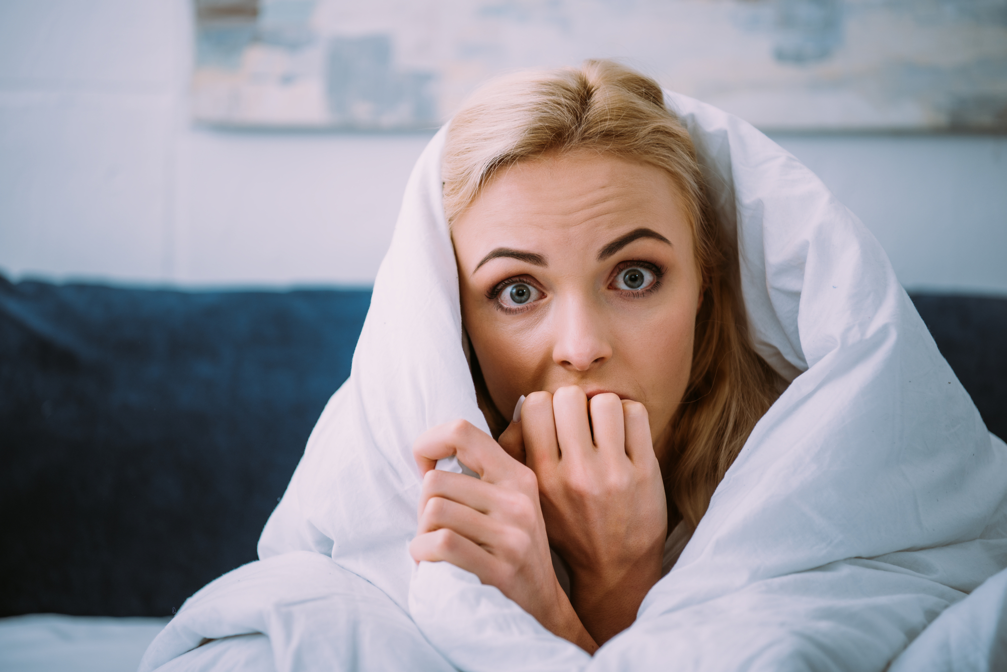 Fearful woman peaking out of a blanket, knuckles to her mouth