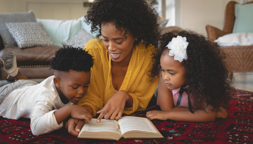 Photo of a mom reading to her little boy and little girl while the boy points to the page.