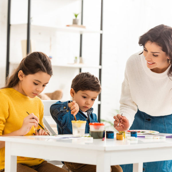 Mom helping kids painting at a table