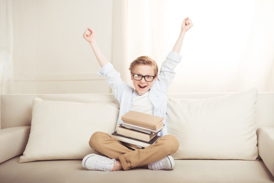 Boy with books that has his arms up in the air like he is happy