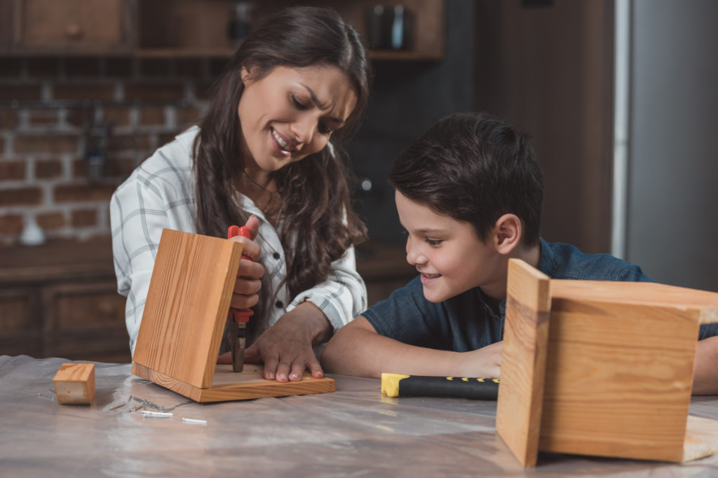 Mother building a bird house with her son. Learning styles are tools to teach our kids.